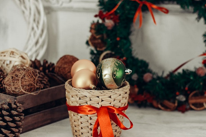 Decorate the wicker basket with Christmas items.